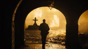 Siluetten av en man mot bakgrunden av brinnande ruiner.