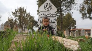 En syrisk flyktingpojke på en begravningsplats i Sarmada, Idlib, där flyktingfamiljer sökt skydd i ett bönerum.