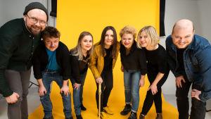 Naisen kosto -podcastin tekijäporukka poseeraa kameralle keltaisen studiotaustan edessä.