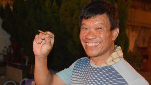 Leende kinesisk man med en cigarill mellan fingrarna.