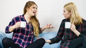 Två kvinnor med kaffekoppar i soffa, den ena gestikulerar och pratar, den andra sitter tyst