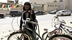 Wadjda (Waad Mohammed) står bredvid en grön cykel och ser drömmande på den.