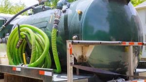 En sugtömningsbil med grön tank och en grön ihoprullad slang bredvid säg.