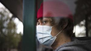 En person med munskydd står på busshållplatsen.