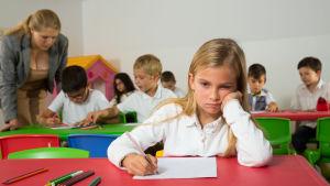 Kuvassa on koulutehtävää tekevä tyttö mietteliään näköisenä. Opettaja neuvoo takana toisia oppilaita.