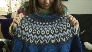 En blå och grå tröja med isländskt mönster hålls upp av en kvinna.