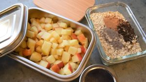 Två matlådor på ett bord i ett kök med äppeltärningar och havregryn