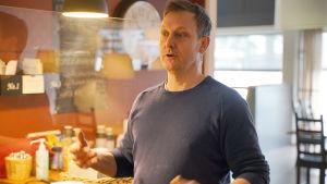 En man står och gestikulerar med armarna samtidigt som han pratar inne i en tom restaurang.