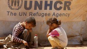 Två barn framför UNHCR:s banderoll.