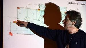 En konsult pekar på en ritning över en skola, med röda prickar.