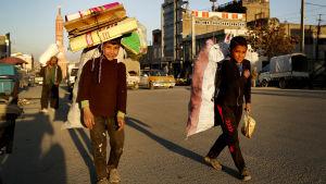Två killar går på gatan i Kabul med stor packning den 26 april 2017