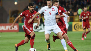 Vitklädd fotbollsspelare dribblar mellan två motståndare.