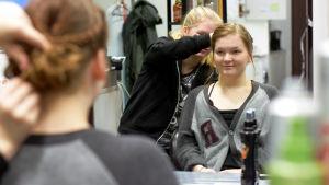 Elin Sigfridsson lagar en håruppsättning på Wilma Westerlund som sitter i en frisörstol.