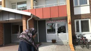En kvinna med huvudduk går förbi ett bostadshus där det står Yalla-trappan ovanför dörren.
