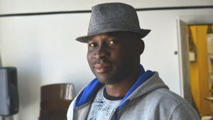 porträtt av francis oyeyiola. han bär en grå hatt, en grå tröja och tittar in i kameran.