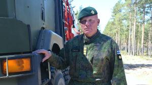 En bild på en man i militärkläder. Han har en grön barett och står lutad mot en lastbil.