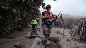 En man bär ett barn udner räddningsoperationen efter vulkanutbrott i juni 2018.