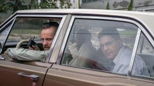 Felix (Jasper Pääkkönen) sitter i en bil med andra klanmedlemmar och ser bistert ut genom bilrutan.