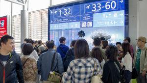 Aasialaisia matkailijoita transithallin opastetaulun luona.