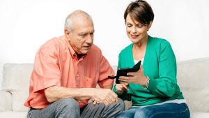 Anna-Liisa Tilus opettaa kännykänkäyttöä iäkkäämmälle herralle.