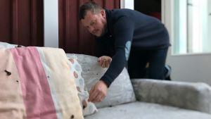 Micke Björklund plockar snäckor från en soffa.