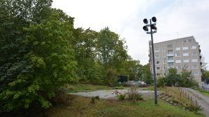 Vy över tom tomtmark i Åbo centrum, ett höghus står i bakgrunden.