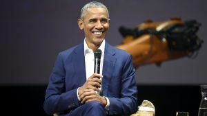 Barack Obama ler stort med en mikrofon i händerna.