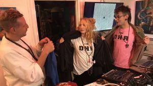 """Tre personer förevisar sina t-shirts med texten """"I am D.N.A."""""""