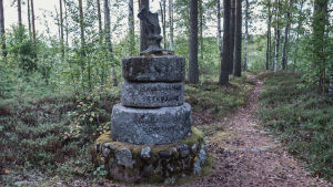 Gravsten bestående av tre ovanpå varandra placerade runda kvarnstenar, överst ett snidarbete i sten.