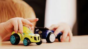 lapsi leikkii autoilla