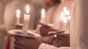 Luciafölje håller levande ljus i händerna.
