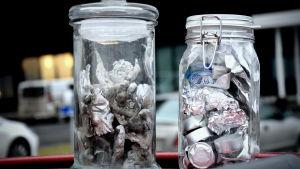 Klimpar av smält aluminium i en burk, samt burklock, ljuskoppar och aluminiumfolie i en burk