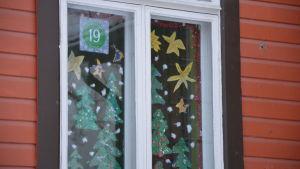 Flera julgranar i papper är fastklistrade i ett fönster.