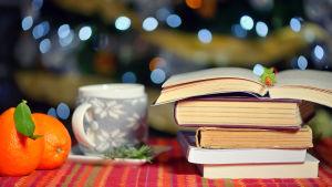 Apelsiner, tekopp och böcker i mysig belysning
