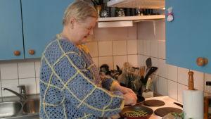 Gunilla Löfman står vid spisen och stäker bönor