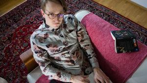 Axel Åhman sitter i en soffa med en dator och tittar in i kameran.