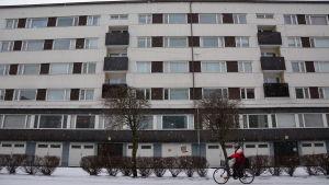 Person cyklar framför höghus en vinterdag i Vasa.