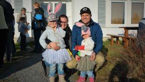 Två barn utklädda till påskhäxor står framför sina föräldrar