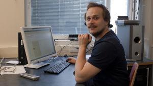 En bild på historielärare Oskar Dikert som sitter vid sitt arbetsbord.