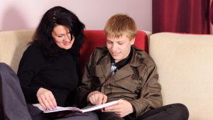 en mamma hjälper sin son med läxläsning