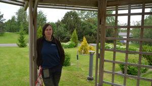Kvinna med blå tröja står i ett lusthus på en begravningsplats.
