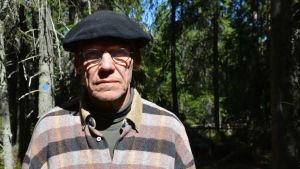 En man som står i en skog med solen i ansiktet
