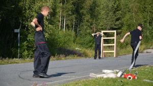 En person springer med en brandslang medan två andra tittar på.