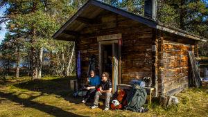 Kaksi retkeilijää istuu eräkämpän rappusilla Urho Kekkosen kansallispuistossa.