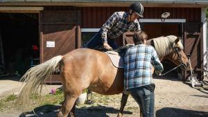 En man tar sig upp på en hästrygg.