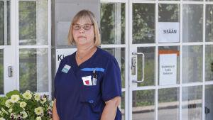 """En kvinna i sjukskötardräkt står framför en entre i glas. På dörren står det """"Entré"""". Kvinnan ser in i kameran. Hon ser nöjd ut."""