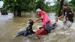 Två män tar sig över översvämmad gata i Myanmar.
