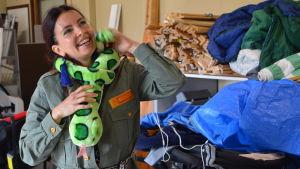 Johanna Kunelius har en grön orm runt sin hals. Det är ett mjukisdjur. Hon skrattar.