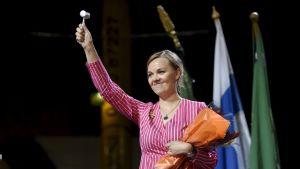 Katri Kulmuni svingar ordförandeklubbar i Kouvola. Hon står på scen med blommor under ena armen och ordförandeklubban höjd i den andra.