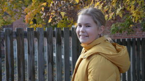 En flicka i en gul jacka ser in i kameran över axeln.
